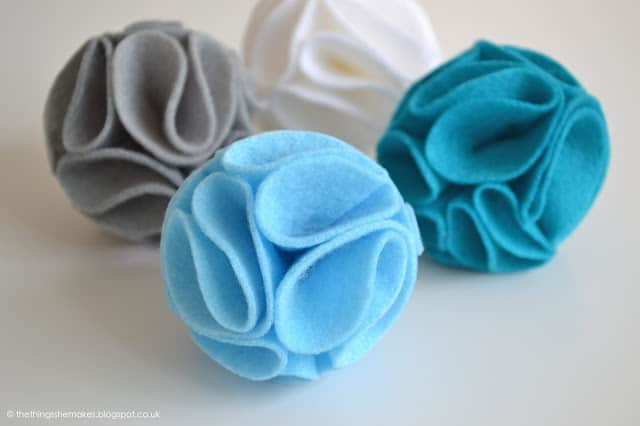 4 felt pom poms in blue, grey and white colors.