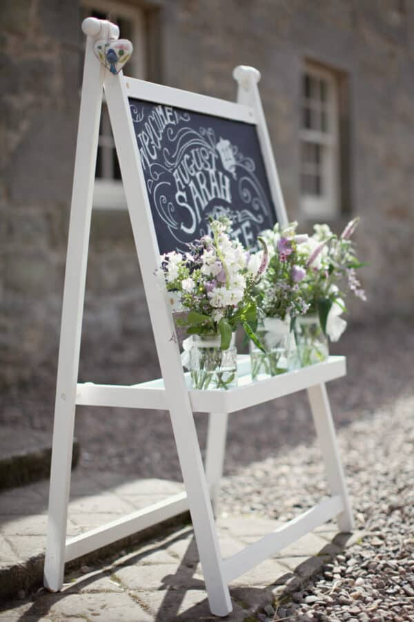 Blackboard with white frame and flowers.
