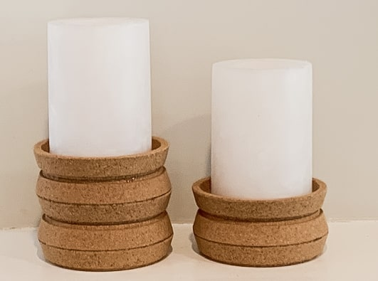 2 cork candlesticks with candles made from IKEA Cork coasters.