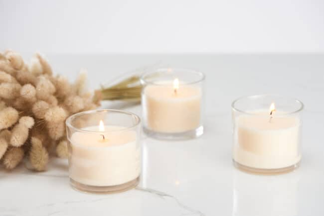 3 white candles in glass containers.
