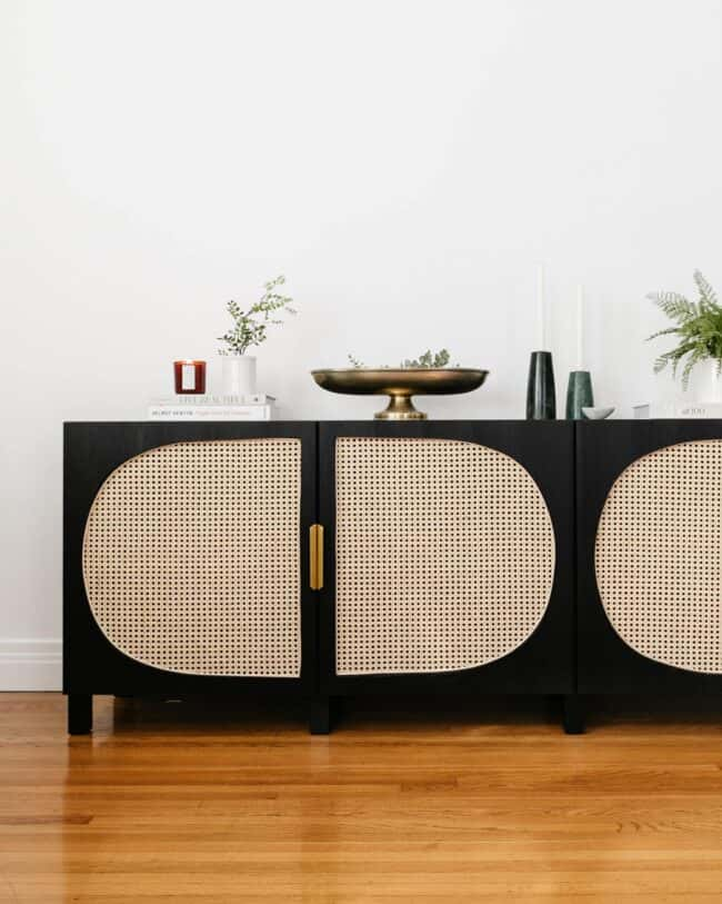 Black cabinet with rattan cane door panels.