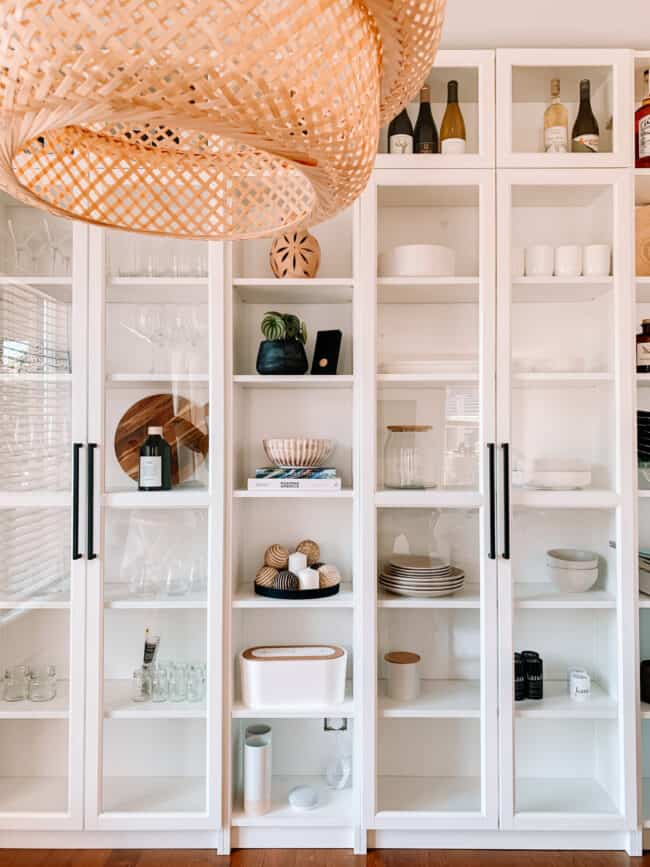 White fitted shelving with glass doors.