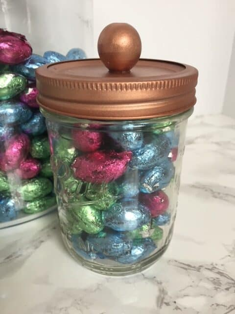 Copper top glass storage jar filled with chocolate easter eggs.