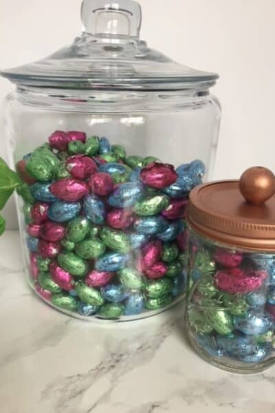 Glass jars full of colored chocolate Easter eggs.