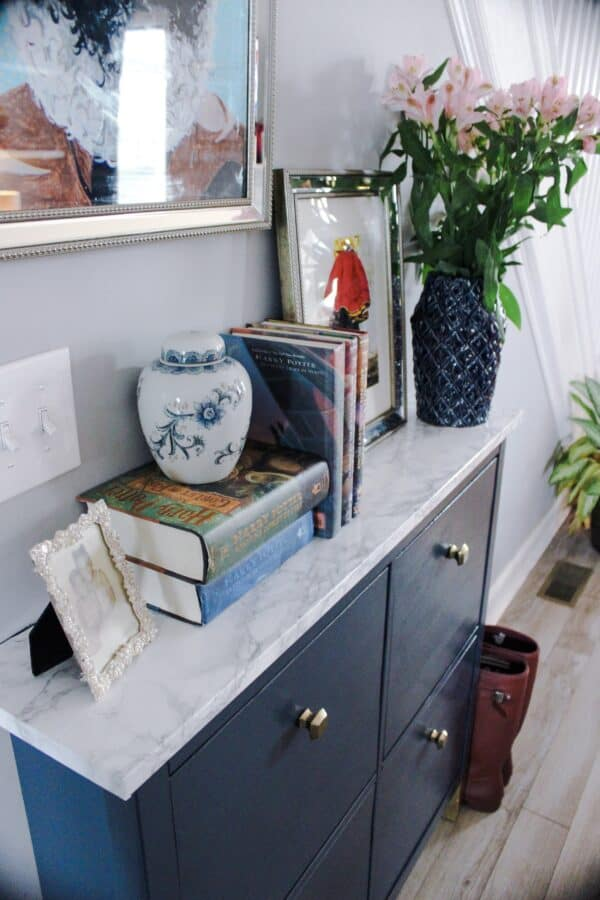 Gray Hemnes shoe storage unit with marble top.
