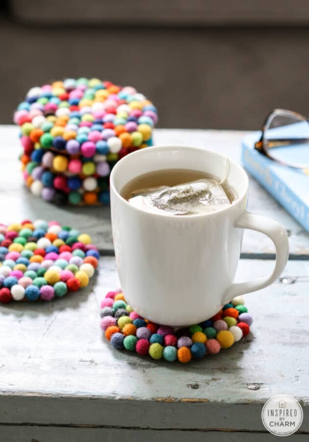 multicolored felt ball coasters with a cup of tea.