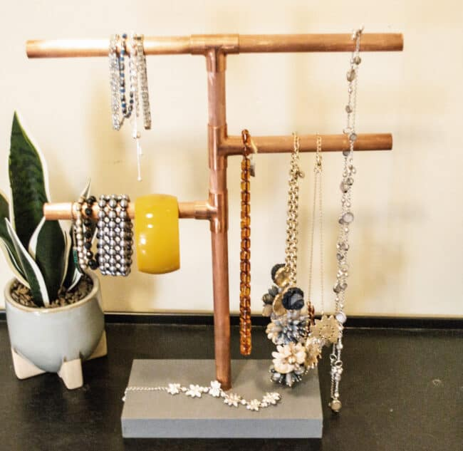 Copper pipe jewelry stand with jewelry.