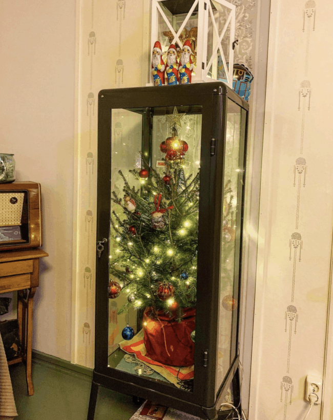 Christmas tree displayed inside a black glass door cabinet.
