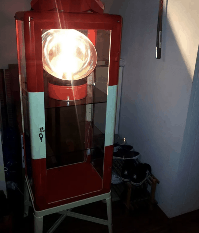 Red and blue lighthouse made from a glass cabinet.