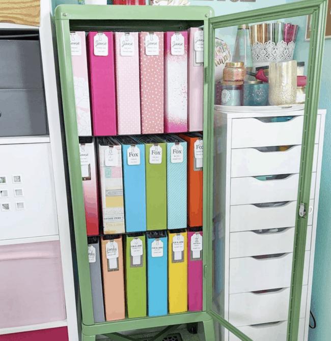 Green glass door cabinet full of colored binders.