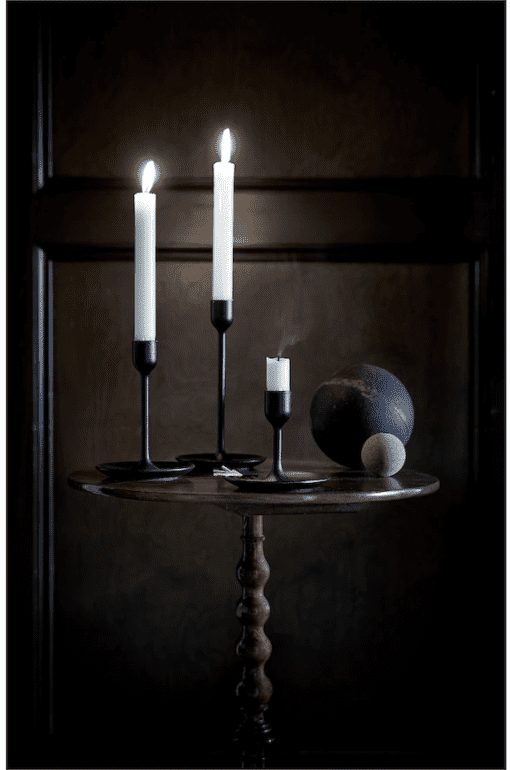 Black candlesticks with lighted candles on a table.