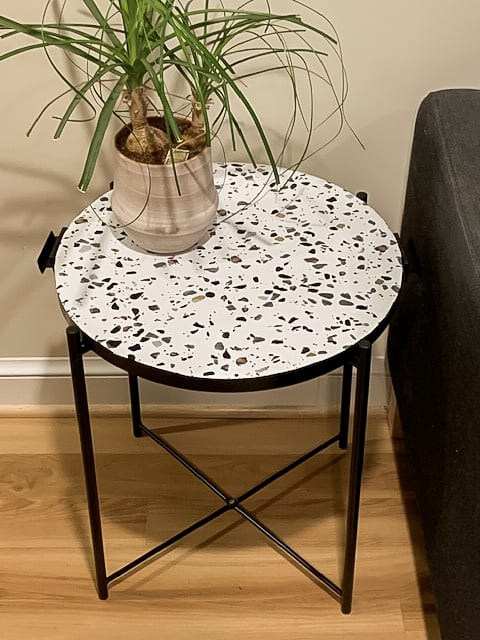 Terrazzo and black side table with plant on top.
