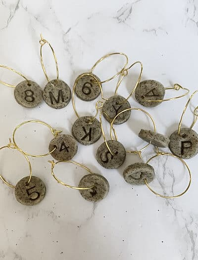 Grey wine glass drink charms on marble surface.