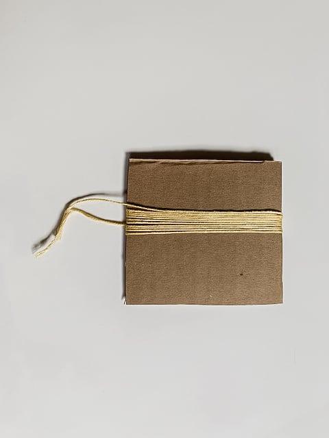 Cartón con hilo envuelto alrededor.