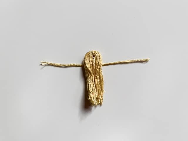 Borla de hilo amarillo atada.