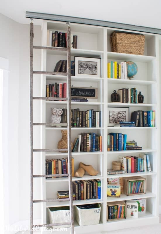 Tall white fitted bookshelves with moving library ladder.