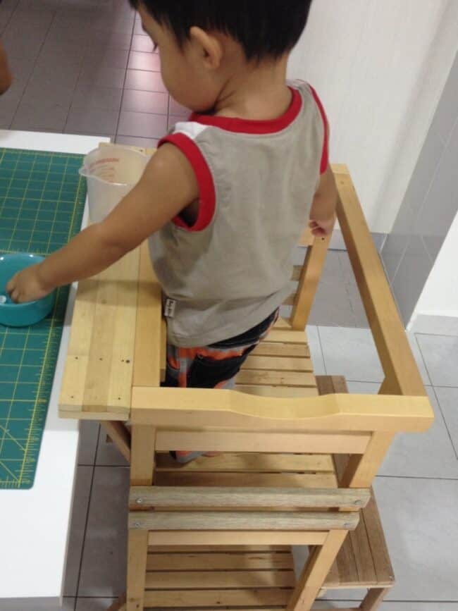 Child standing on wooden learning tower.